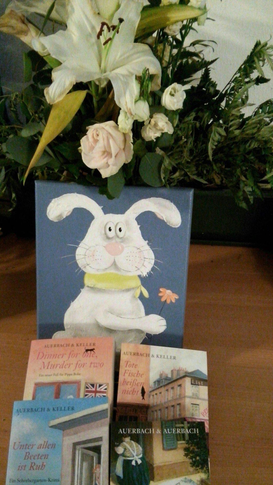 ein großer Blumenstrauß, davor das Bild mit dem Hasen und davor aufgefächert vier Bücher